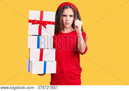 Cute hispanic child girl holding gift annoyed and frustrated shouting with anger, yelling crazy with anger and hand raised