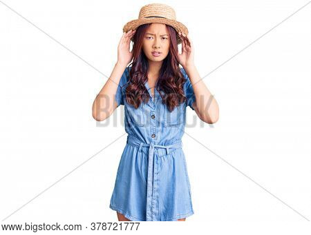 Young beautiful chinese girl wearing summer hat trying to hear both hands on ear gesture, curious for gossip. hearing problem, deaf