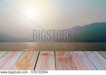 An Empty Wooden Table With The Light Of The Sun And A Natural Pool With Mountains And Skies, This Vi