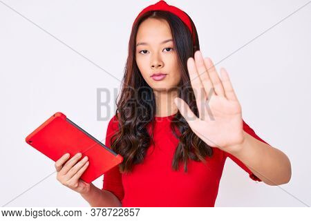 Young beautiful chinese girl holding touchpad with open hand doing stop sign with serious and confident expression, defense gesture