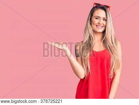 Young beautiful blonde woman wearing sleeveless t-shirt and sunglasses smiling cheerful presenting and pointing with palm of hand looking at the camera.