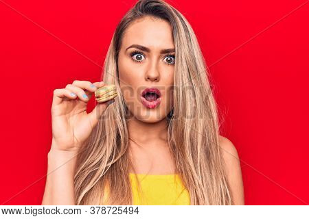 Young beautiful blonde woman eating french dessert macaron over isolated red background scared and amazed with open mouth for surprise, disbelief face