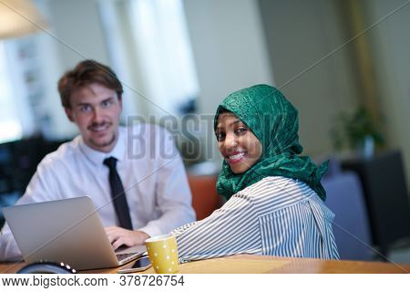 international multicultural business team.man and african muslim woman with green hijab working together using mobile phone and laptop computer in relaxation area at modern open plan startup office