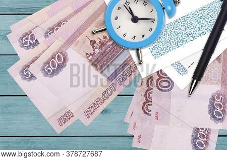 500 Russian Rubles Bills And Alarm Clock With Pen And Envelopes. Tax Season Concept, Payment Deadlin
