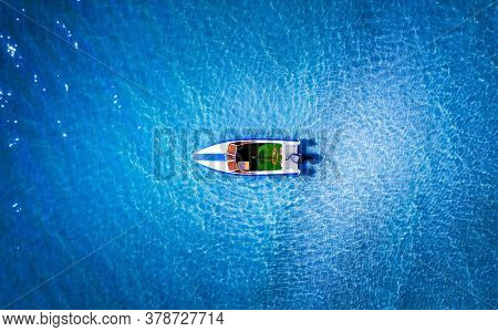 Top View Of A White Boat In The Blue Sea.