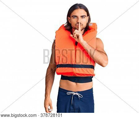 Young handsome man wearing nautical lifejacket asking to be quiet with finger on lips. silence and secret concept.