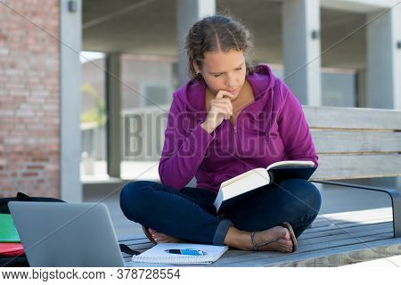 Beautiful German Female Student Learning With Book And Computer In Front Of School Building Outdoor