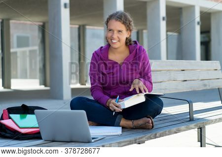 Pretty German Female Student Learning With Book And Computer In Front Of School Building Outdoor In