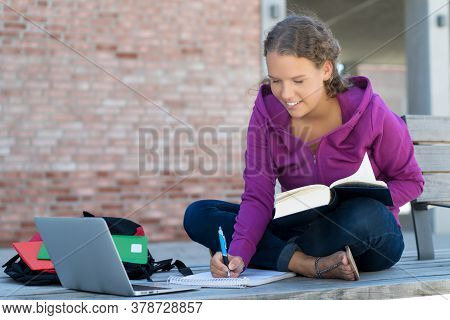 Young German Female Student Learning With Book And Computer In Front Of School Building Outdoor In S