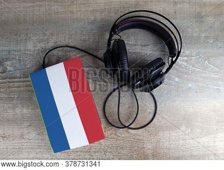 Headphones And Book. The Book Has A Cover In The Form Of Netherlands Flag. Concept Audiobooks. Learn