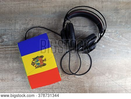 Headphones And Book. The Book Has A Cover In The Form Of Moldova Flag. Concept Audiobooks. Learning