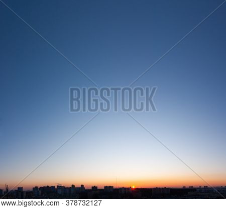 Bright Clear Blue Sky And Sun In Sunset Over Buildings Of City, Bright Panorama Landscape Background