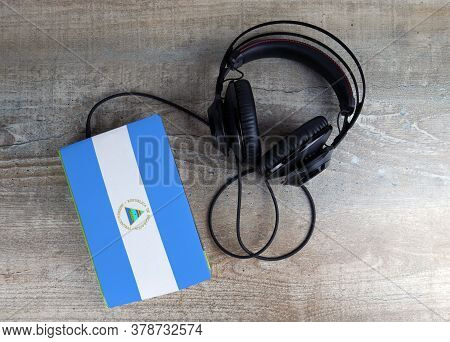 Headphones And Book. The Book Has A Cover In The Form Of Nicaragua Flag. Concept Audiobooks. Learnin