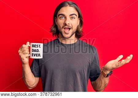 Young handsome man drinking mug of coffe with best dad ever message celebrating achievement with happy smile and winner expression with raised hand