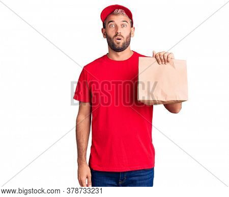 Young handsome blond man holding delivery paper bag scared and amazed with open mouth for surprise, disbelief face