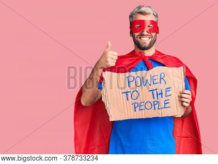 Young blond man wearing super hero custome holding power to the people cardboard banner smiling happy and positive, thumb up doing excellent and approval sign