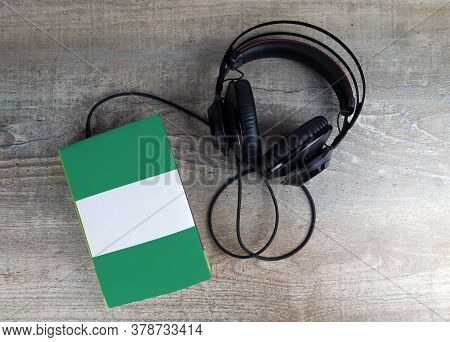 Headphones And Book. The Book Has A Cover In The Form Of Nigeria Flag. Concept Audiobooks. Learning