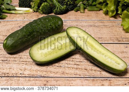 Green Healthy Cucumbers On A Brown Wooden Background. Products For The Keto Diet, Gluten-free Diet A