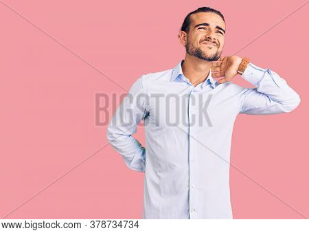 Young handsome man wearing business clothes suffering of neck ache injury, touching neck with hand, muscular pain