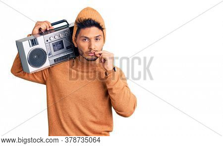 Handsome latin american young man holding boombox, listening to music mouth and lips shut as zip with fingers. secret and silent, taboo talking