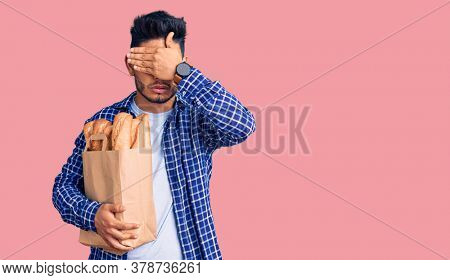 Handsome latin american young man holding paper bag with bread covering eyes with hand, looking serious and sad. sightless, hiding and rejection concept