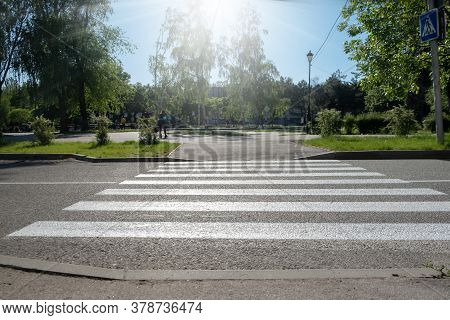 A Crosswalk For Pedestrians Crossing The Street. Empty Crosswalk To The Park