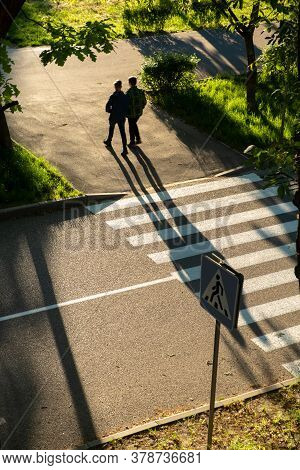 Crosswalk With Shadows Of Pedestrians. Couple Walking Across The Crosswalk At The Junction Street Of