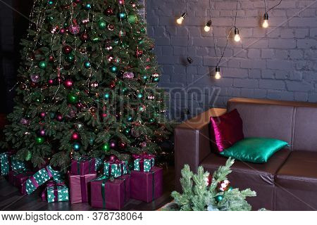 Christmas Tree And Leather Brown Sofa. Pink And Green Gifts With Ribbons Underneath. New Year, Happy