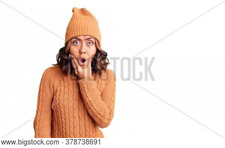 Young beautiful mixed race woman wearing wool sweater and winter hat looking fascinated with disbelief, surprise and amazed expression with hands on chin