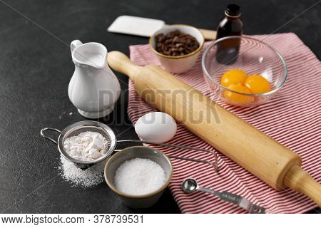 cooking food and culinary concept - rolling pin, milk, eggs, flour and chocolate on table