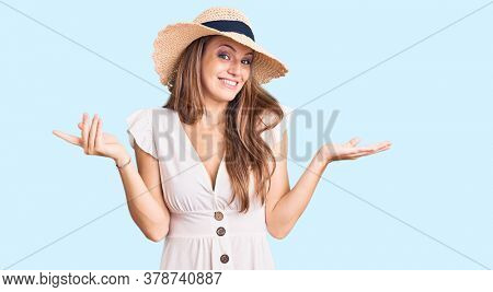 Young beautiful blonde woman wearing summer dress and hat clueless and confused expression with arms and hands raised. doubt concept.
