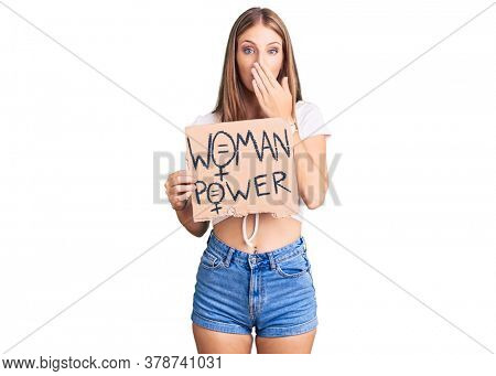 Young beautiful blonde woman holding woman power banner covering mouth with hand, shocked and afraid for mistake. surprised expression