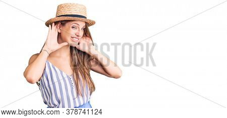 Young beautiful blonde woman wearing summer hat trying to hear both hands on ear gesture, curious for gossip. hearing problem, deaf