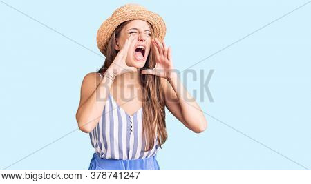 Young beautiful blonde woman wearing summer hat shouting angry out loud with hands over mouth