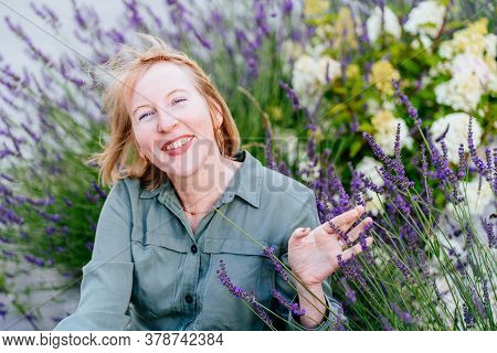 Mature Woman Feeling Good, Enjoying The Scent Of Lavender Flowers. Happy Successful Blond Middle Age