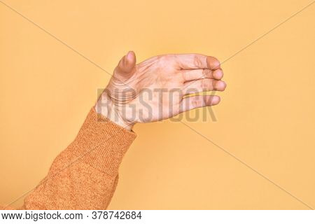 Hand of caucasian young man showing fingers over isolated yellow background holding invisible object, empty hand doing clipping and grabbing gesture