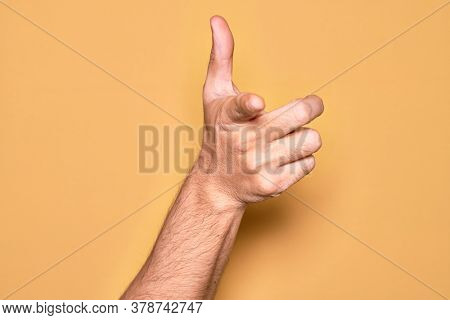 Hand of caucasian young man showing fingers over isolated yellow background pointing forefinger to the camera, choosing and indicating towards direction
