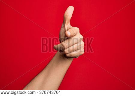 Hand of caucasian young man showing fingers over isolated red background pointing forefinger to the camera, choosing and indicating towards direction