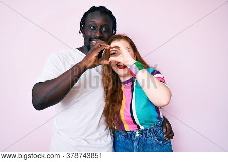 Interracial couple wearing casual clothes doing heart shape with hand and fingers smiling looking through sign
