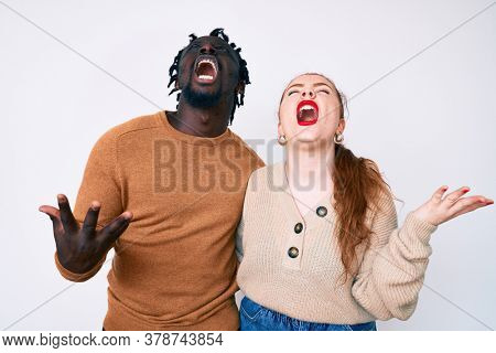 Interracial couple wearing casual clothes crazy and mad shouting and yelling with aggressive expression and arms raised. frustration concept.