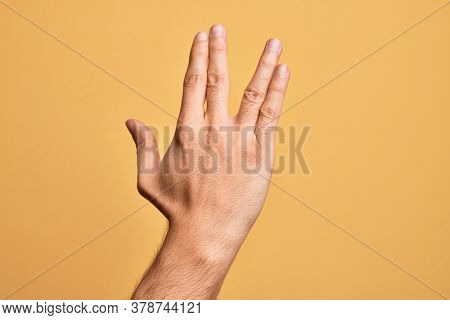 Hand of caucasian young man showing fingers over isolated yellow background greeting doing Vulcan salute, showing back of the hand and fingers, freak culture