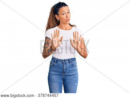 Young hispanic woman with tattoo wearing casual white tshirt moving away hands palms showing refusal and denial with afraid and disgusting expression. stop and forbidden.