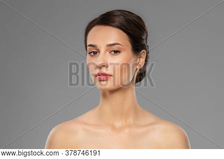 beauty, bodycare and people concept - beautiful young woman with bare shoulder over grey background
