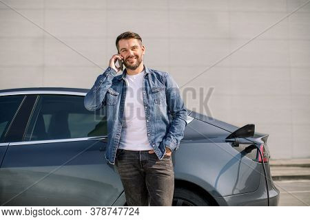 Smiling Caucasian Man In Casual Wear Talking Phone While Leaning On His Luxury New Electric Car, Sta