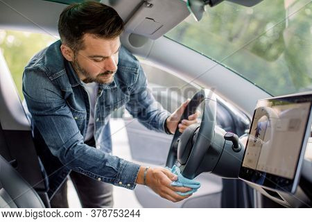 Cleaning Of Car Interior, Car Detailing Concept. Young Caucasian Man In Casual Wear Washes A Car Int