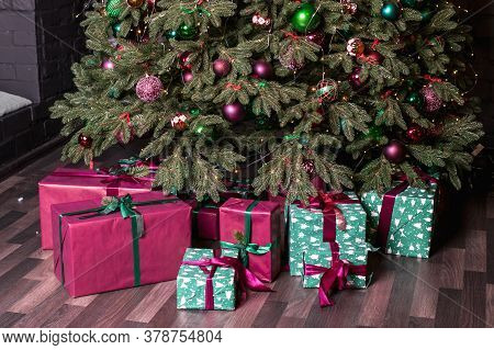 Christmas Tree And Pink And Green Gifts With Ribbons Underneath. New Year, Happy Childhood, Santa Cl