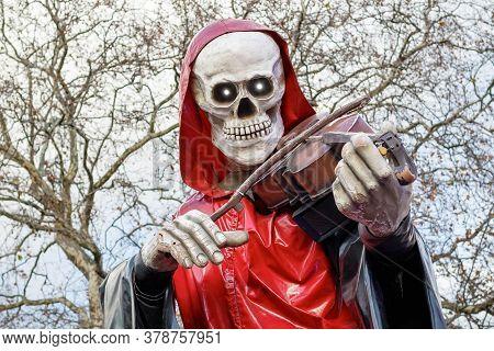 London, Uk - November 25, 2019 - Grim Reaper, A Skeletal Figure Playing The Violin, Outside Haunted