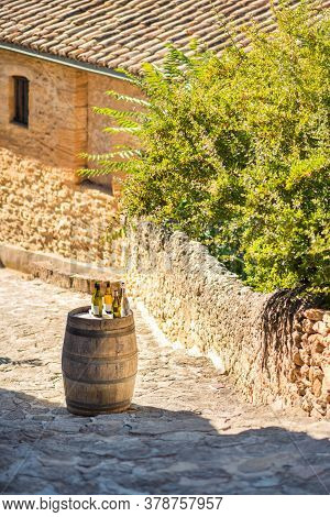 Vertical Picture With Wooden Barrel And Different Wine Bottles On It In Courtyard Of Old Medieval St