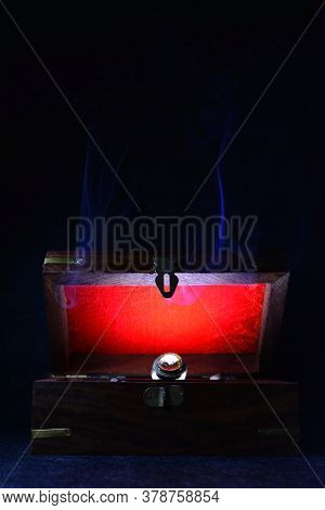 Antique Retro Wooden Box Ajar With A Jewellry Ring And A Red Light Inside It On A Dark Background