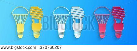 Paper Cut Economical Led Illuminated Lightbulb And Fluorescent Light Bulb Icon Isolated On Blue Back